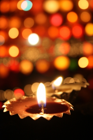 Traditional lamp lit on the blur of colorful lights on the festive occassion of Diwali often known as