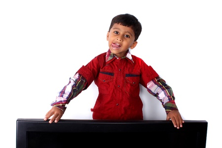 joking: A cute Indian boy fooling around his television set.