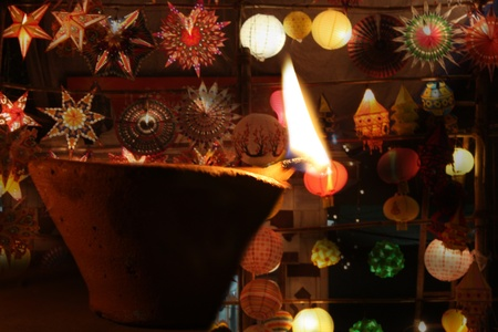 A traditional oil lamp lit in front of beautiful arrangement of sky lanterns, during the festive occassion of Diwali in India.