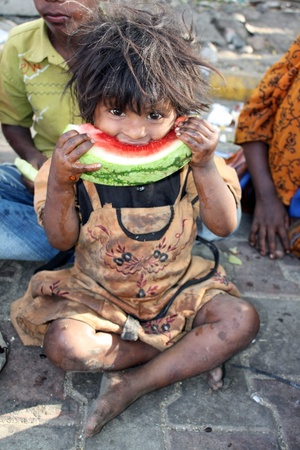 A poor girl from India hungrily eating a watermelon.
