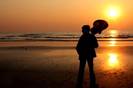 hombre solitario: Una silueta de un guitarrista en una playa solitaria.
