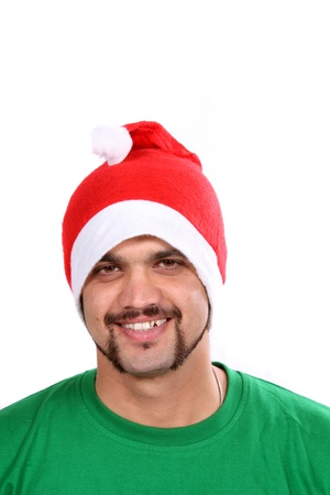 A young Indian guy wearing a santa hat during Christmas in India, on white studio background. photo
