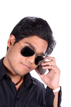A young Indian guy talking on the cellphone, on white studio background. photo