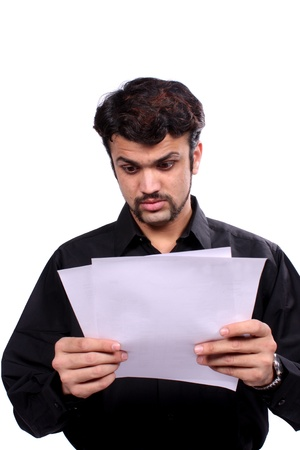 An Indian man getting shocked looking at the telephone and electricity bills, on white studio background. photo