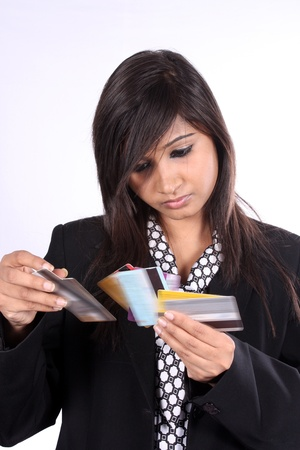 creditcards: A young Indian businesswoman checking different credit cards, on white studio background.