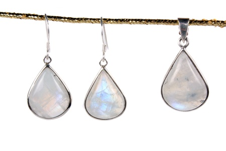 A set of jewelery made of moonstones hanging on a golden chord, isolated on white studio background.