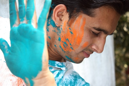 A young Indian man uses his hand to stop holi colors getting on to his face  photo