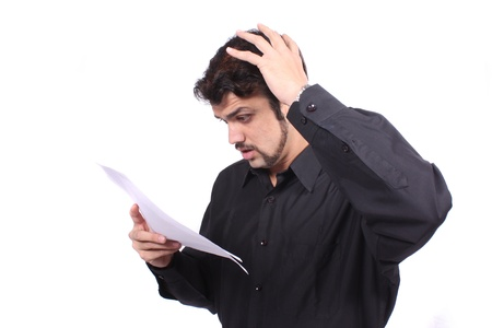 A young Indian man shocked looking at his high phone   power bills or invoices, on white studio background  Stock Photo