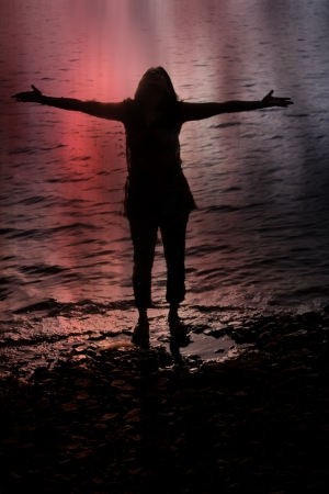 blissful: A metaphorical spiritual image of a silhouetted woman experiencing blissful energies on the riverside