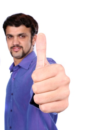 An Indian guy wishing good luck with a thumbs up sign, on white studio background  Focus on hand  photo