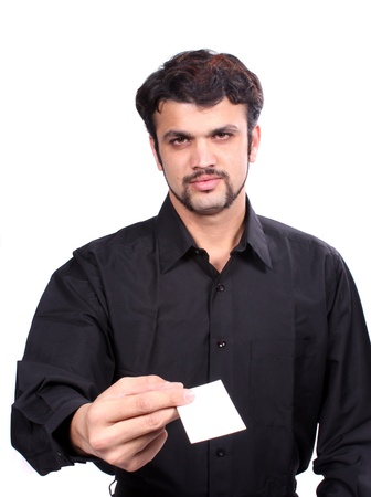 A young Indian guy giving his new business card, focus on the hand and card  Card left blank for designers editing  photo