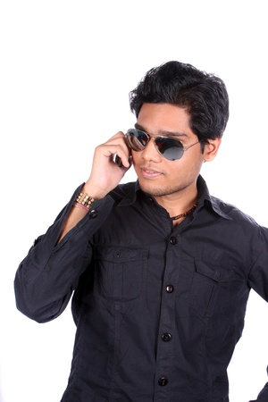 A young Indian guy wearing sunglasses stylishly talking on the phone, on white studio background  photo
