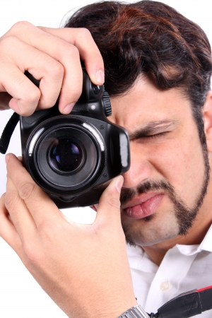 accurately: A young Indian photographer closing his eye to focus his camera accurately