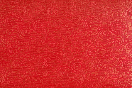 A background of a red fabric with an ethnic Indian design in gold