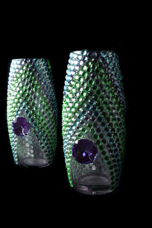 artisitc: Beautiful designer vases studded with colorful artificial jewels, on black studio background