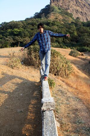 balance beam: A young Indian man trying to balance himself while walking on a cement beam