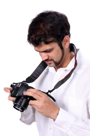 A young Indian professional photographer checking the quality of the photographs after clicking them, on white studio background. photo
