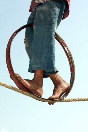 the trapeze: A closeup view of the feet of a poor Indian trapeze girl, whose daily living hangs on the balance of her act on the rope. The image also depicts progress based on the right balance. Stock Photo