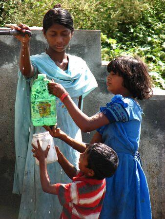 gente pobre: Los ni�os pobres luchan por obtener las �ltimas gotas de agua del grifo, debido a la escasez de agua en la India