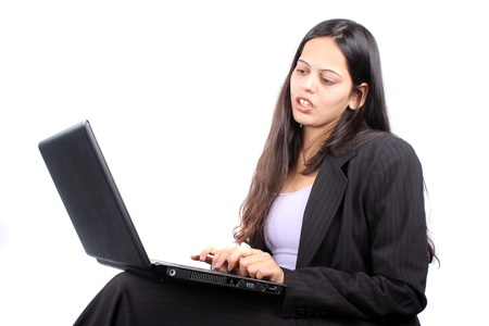 An young Indian businesswoman working on her laptop, on white studio background  photo