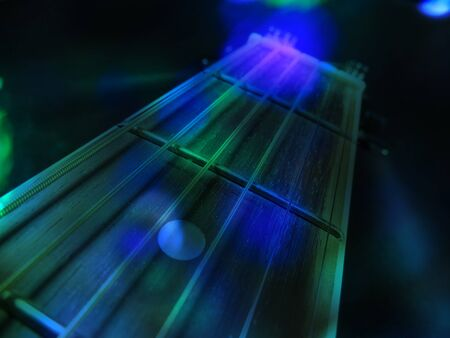 An abstract background of an acoustic guitar in green and blue concert lights.                                Stock Photo