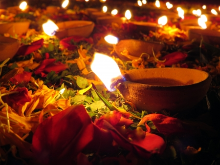 Traditional earthen oil lamps lit with flowers and petals for a holy ritual during Diwali festival in India.                                photo