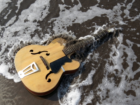 metaphorical: A metaphorical image of an old guitar being washed away by sea waves depicting the end or death of an era of music leaving a legacy behind Stock Photo