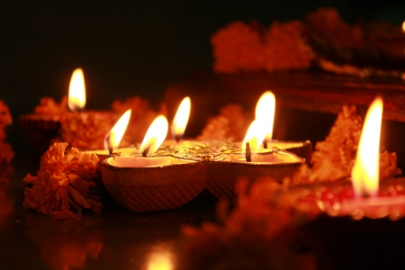 spiritualism: Earthen oil lamps lit with flowers during the performance of a hindu ritual.