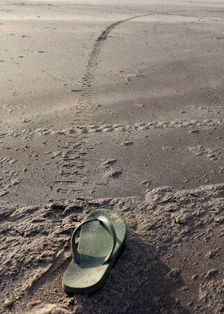 metaphorical: A metaphorical image of a lone flip flop with a long sand track ahead of it  Stock Photo