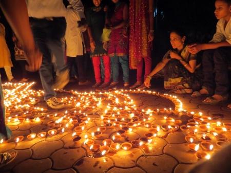 earthen: Persone provenienti da India luce fino lampade di terra tradizionali in occasione del Diwali celebrazioni di festival Editoriali