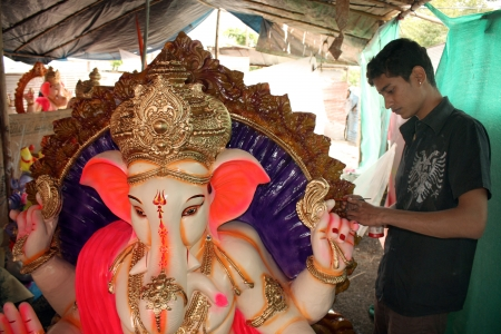 adds: An artist adds the finishing touches to a huge Lord Ganesha idol on the eve of Ganesh festival in India. Editorial