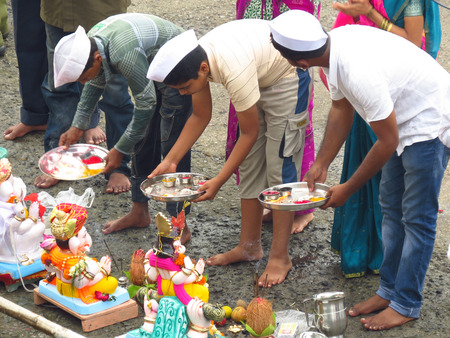 submerging: Indian people traditionally perform a ritual to end the 10-day long Ganesh festival before submerging the deity idols in a river.