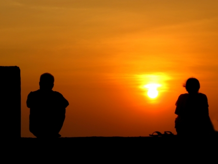 sad lonely: A metaphorical image of the silhouettes of a seperated couple on the backdrop of a sunset.