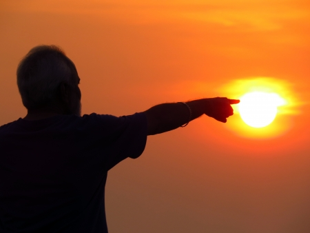 guiding: A metaphorical image showing a wide old Indian man pointing at the Sun, showing the concept of a pathfinder or leader.