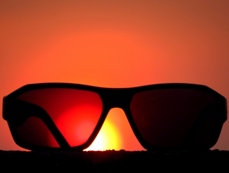evenings: A metaphorical picture of sunglasses against the backdrop of the setting sun conceptualizing a holiday.