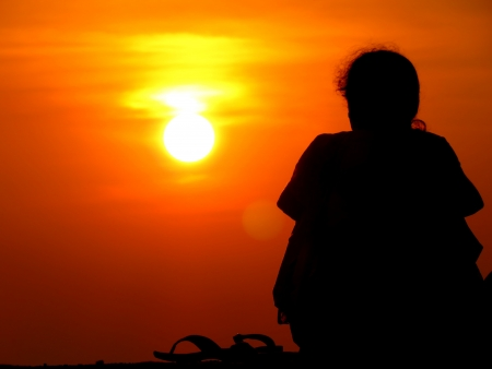 sunsets: A silhouette of lonely woman sitting alone watching the sunset. Stock Photo