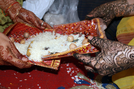 rituals: Mehendi decorated Hands of two ladies during a traditional ritual performed in a Jain marriage Stock Photo