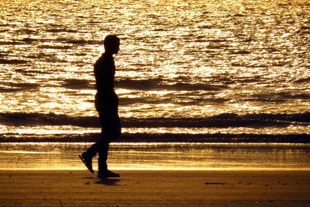 lonely man: A lonely man taking a walk on the beach in the evening Stock Photo