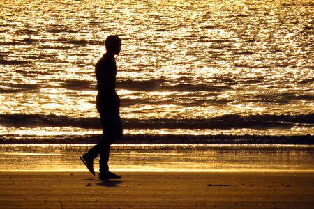 hombre solitario: Un hombre solo dar un paseo en la playa por la noche