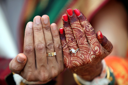 The wedding rings on the hands of an Indian bride and groom