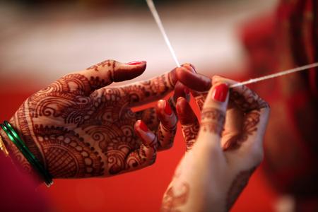 結婚式: 宗教スレッドは、伝統的なヒンドゥー教の結婚式に親族の手でタイトな開催。