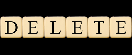 deletion: A delete word made from scrabble tiles on black studio background.