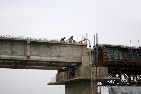 constructing: Workers working on a cloudy day while constructing a huge bridge in India. Stock Photo