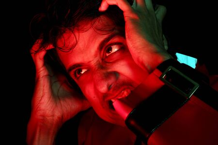 raged: An Indian man getting frustrated and angry, in dramatic studio lights.
