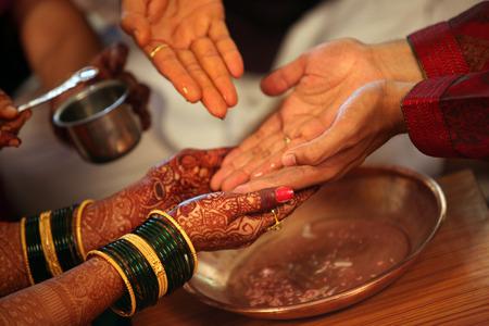 mariage: Les mains de la mariée et le marié d'être lavés avec de l'eau bénite dans un rituel traditionnel de mariage hindou Banque d'images