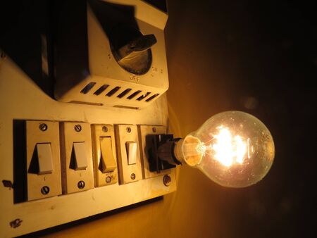 regulator: An old switchboard with fan regulator and tungsten bulb.