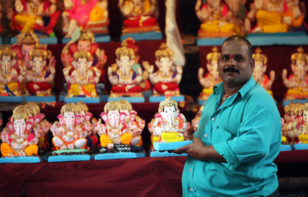 involves: A man selling Lord Ganesh idols on the eve of Ganesh festival in India. The festival involves thousands of visitors from all over the world every year, in the main celebration city - Pune.