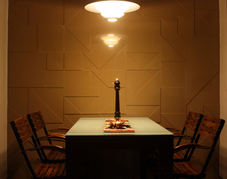 dining table and chairs: A beautiful dining table with four chairs with a lamp above, in a house.