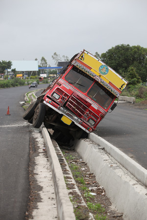 carelessness: An accident of a truck stuck in the rainwater drain passage on an Indian highway Stock Photo