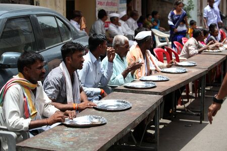 india food: Pune, India - July 11, 2015: Indian pilgrims sitting on table on a sunny day, waiting for food to be served. Stock Photo